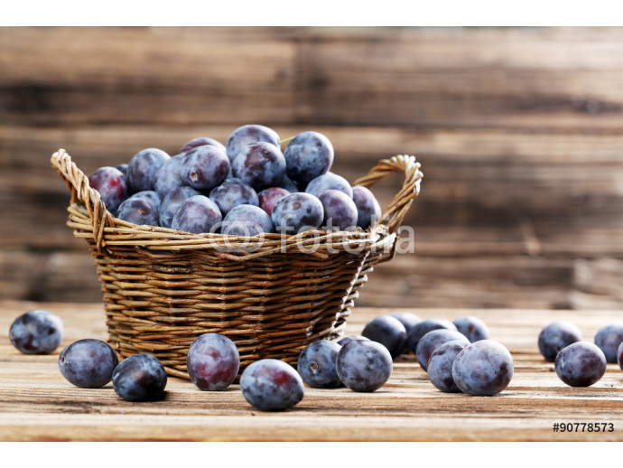 Fresh plums in basket on brown wooden background 64238