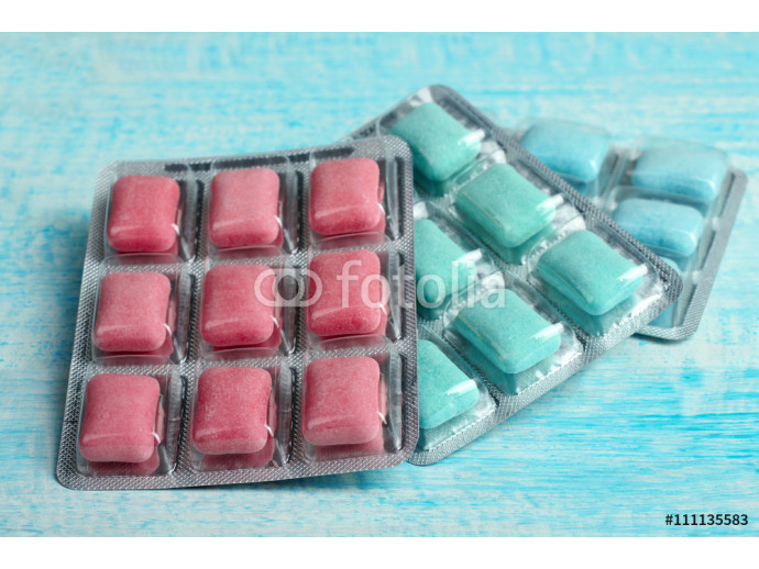 a pack of chewing gum of different colors in form of cushions on blue wooden background 64238
