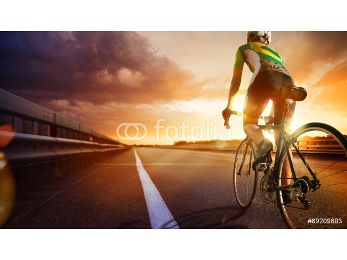 Cyclist riding a bike on an open road to the sunset 64238
