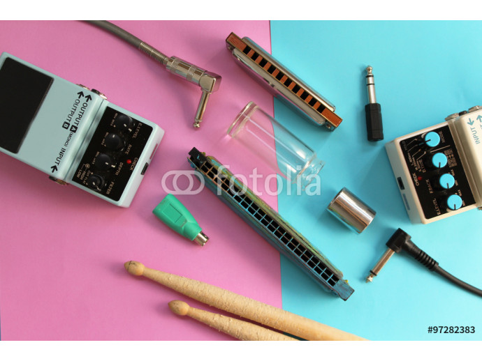 Music concept - guitar pedals, drum sticks, harmonica, audio plug, guitar slide and guitar picks on half blue half pink background 64238