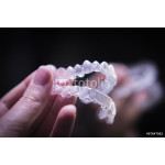 Woman hand holding invisible orthodontics 64238