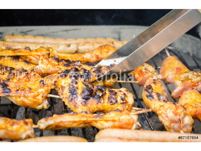 Sausages and chicken wings on smoking grill barbeque 64238