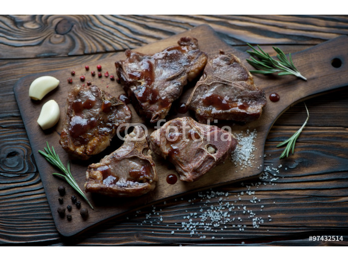 Rustic wooden chopping board with grilled T-bone lamb steaks 64238