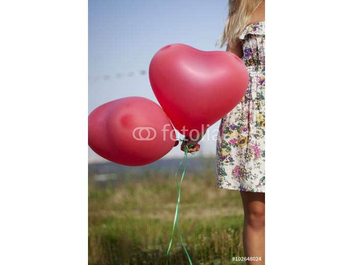 A girl holding two balloons in shape of heart 64238