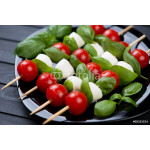 Kebabs with mozzarella, red tomatoes and green basil on a plate 64238