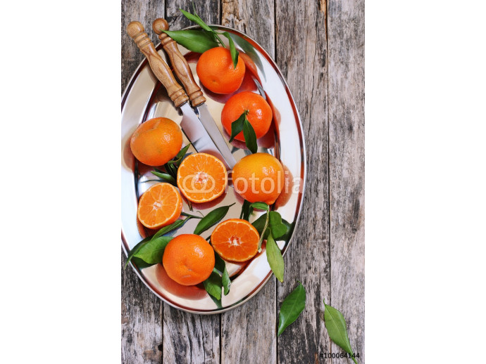 Fresh tangerines with leaves on a rustic wooden table.Selective focus. 64238