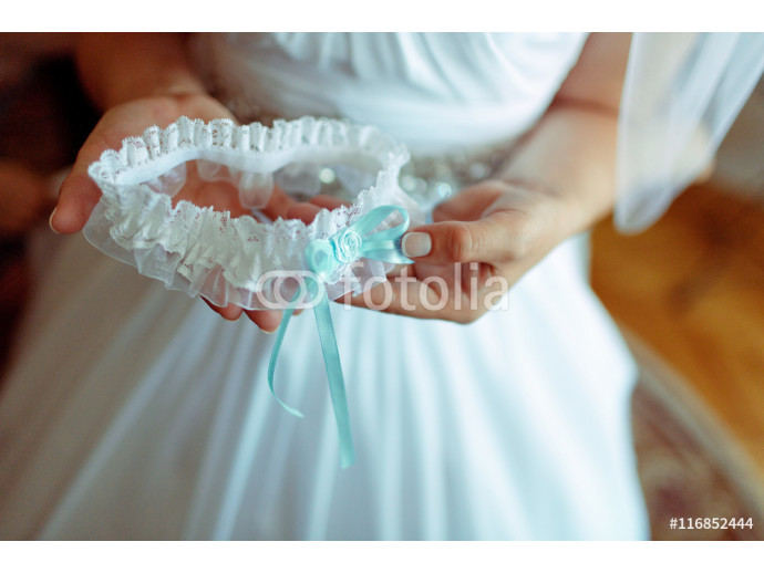 Fototapeta Bride holds a garter with a blue ribbon in her arms 64238