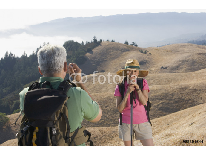 Senior man taking a picture of his wife on a hike 64238