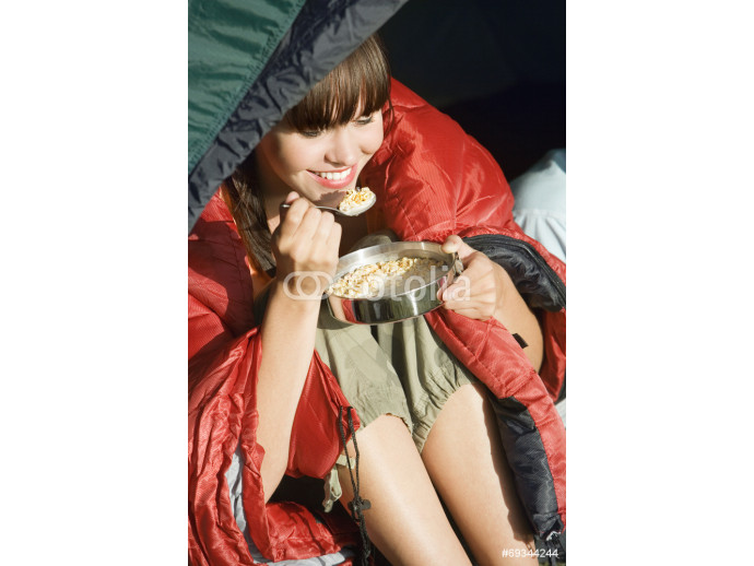 Young woman, wrapped in red sleeping bag, sitting in tent on camping trip, eating cereal, smiling, close-up 64238