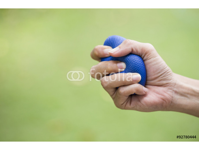 Woman hand squeezing a stress ball 64238