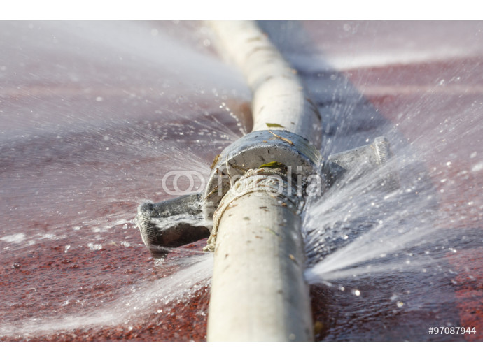 wasting water - water leaking from hole in a hose 64238