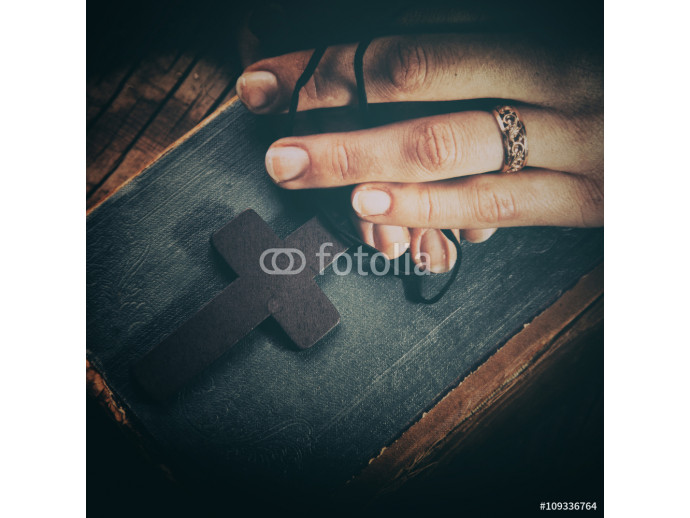 closeup of hands holding vintage cross on Bible 64238