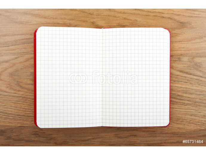 Notebook with square grid on wooden table. 64238