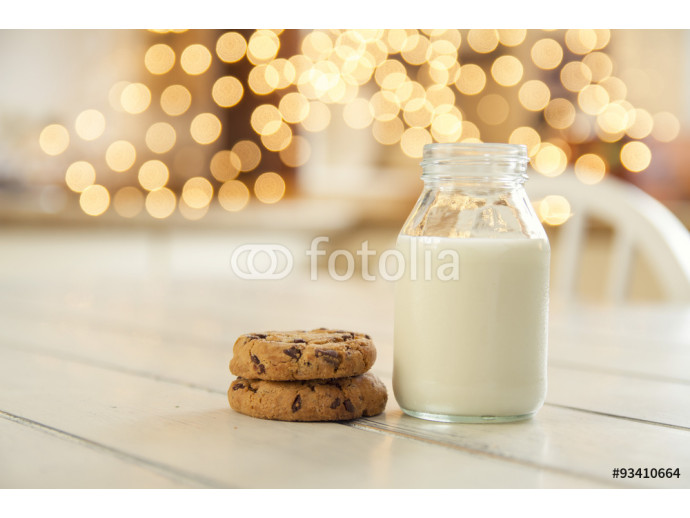 A school milk bottle and two chocolate chip cookies. Christmas lights in the background 64238