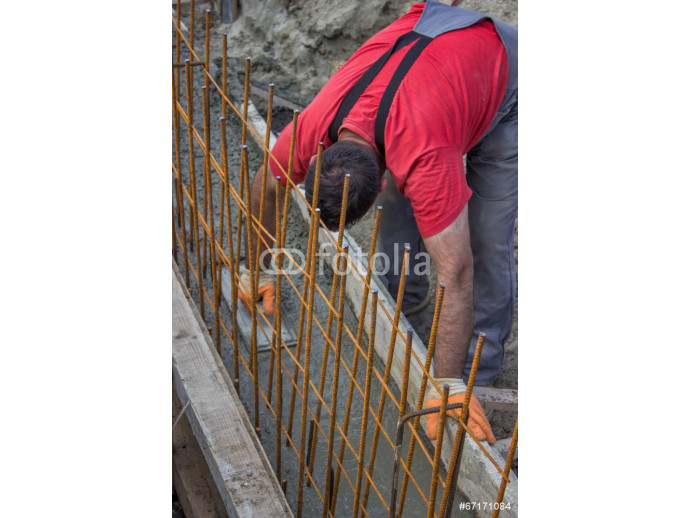 Construction worker smooth fresh concrete with trowel in a ditch 64238