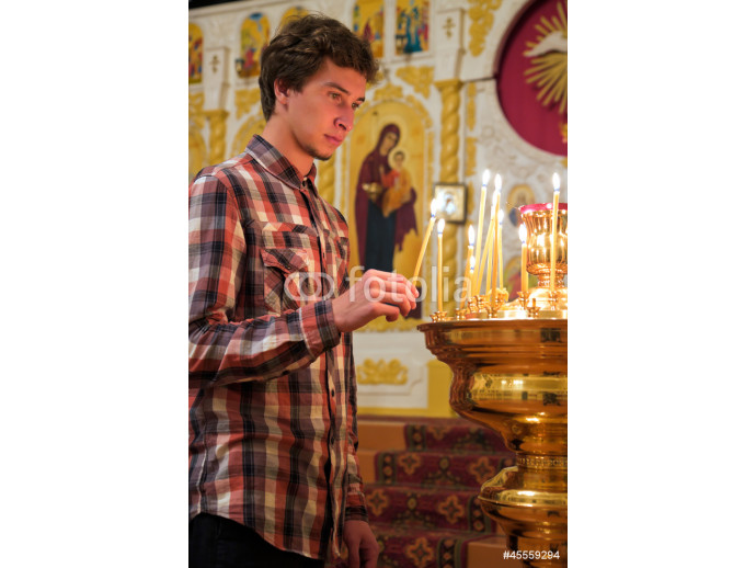Young man lighting a candle in the church. 64238