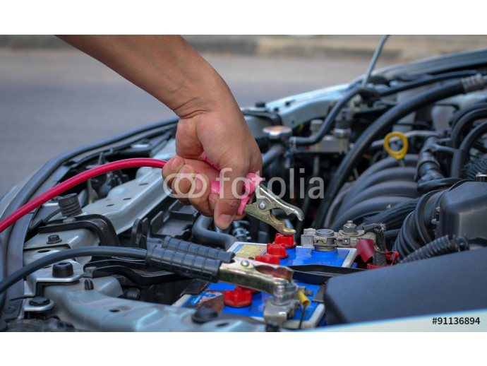 Jumper cables charging battery on a car 64238