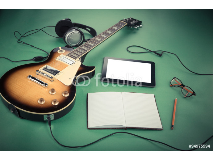 Electric guitar with notepad and old camera on green background 64238