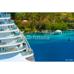 Side of a cruise ship with trees and ocean in background 64238