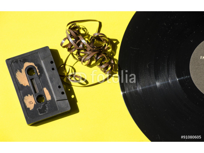 cassette and vinyl record on a colored background yellow retro 64238