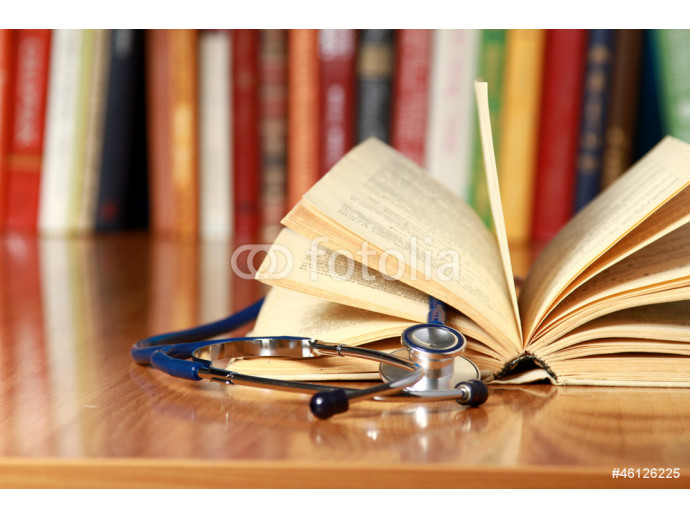 A stethoscope is lying with a book on the desk against books 64238