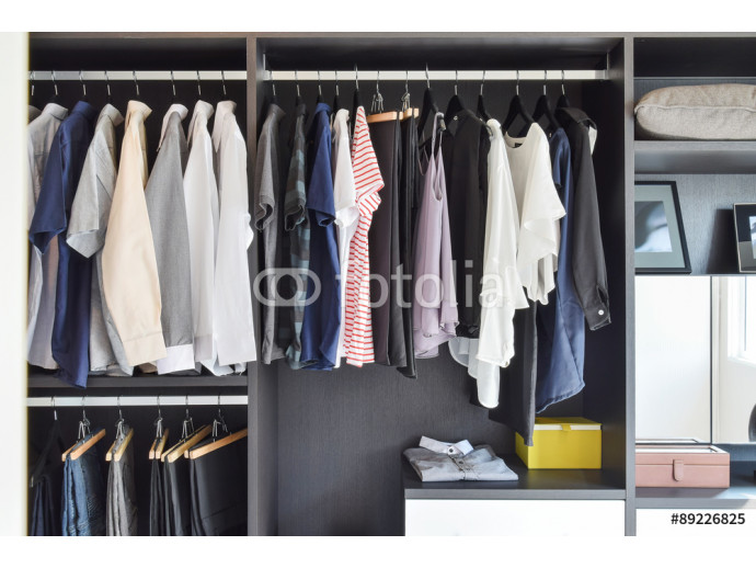 modern closet with row of cloths hanging in black wardrobe 64238