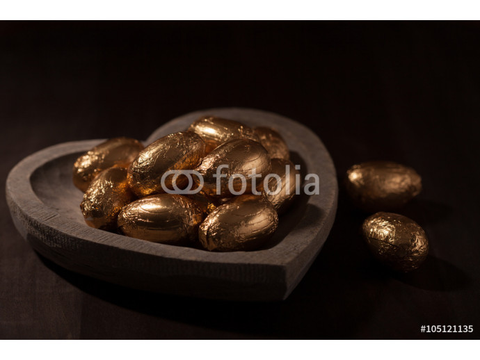 Close-up of Easter eggs in gold foil in a heart shaped wooden bowl against a dark background.  64238