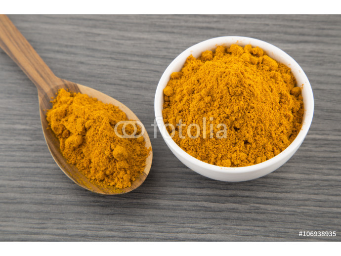 Turmeric powder in bowl and wooden spoon 64238