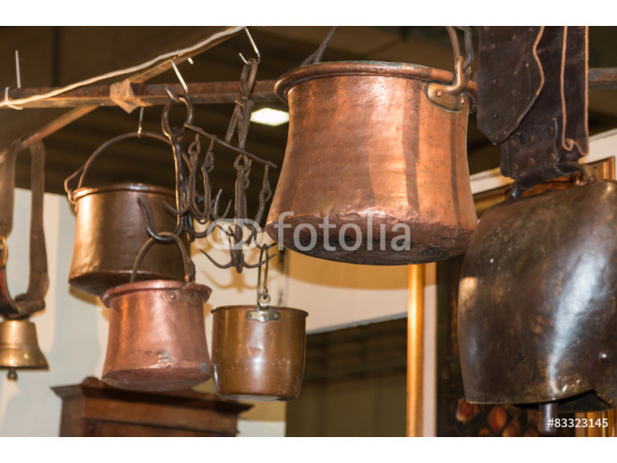 old copper pots hanged on iron hooks 64238
