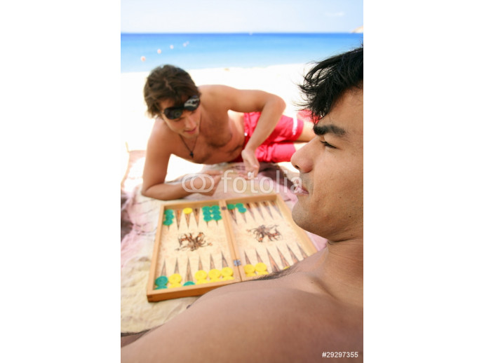 Two men on beach playing backgammon 64238