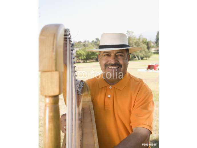 Middle-aged Hispanic man playing harp outdoors 64238