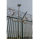 Green fence with razor wire and floodlights guarding French ferr 64238