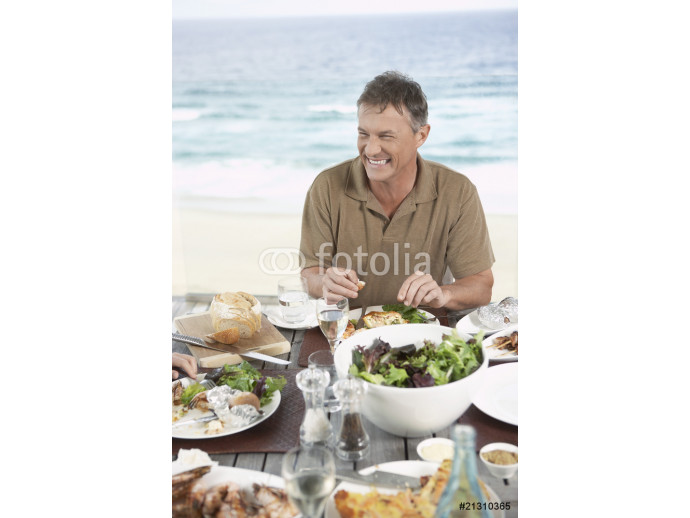 smiling man eating meal outside near the sea 64238