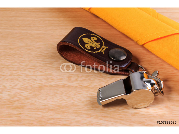 Metal whistle with yellow scout scarf on wooden background. 64238