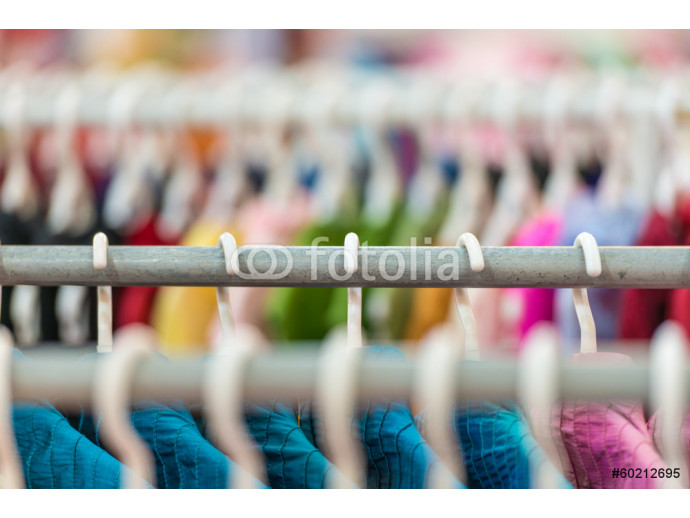 Rows of colorful clothes on hangers at shop. 64238