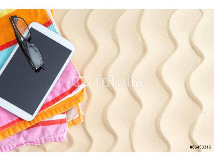 Tablet and glasses on a colorful beach towel 64238