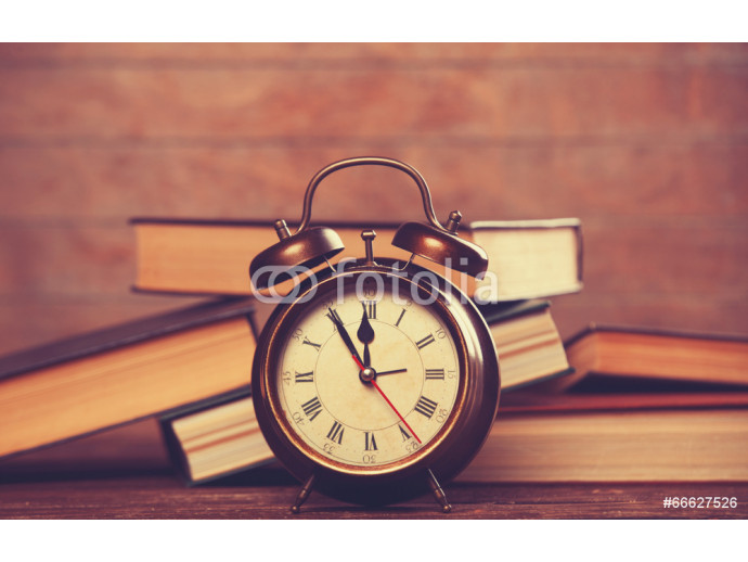 Alarm clock and books on wooden table. 64238
