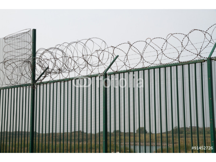 Green fence with razor wire guarding French ferry terminal. 64238