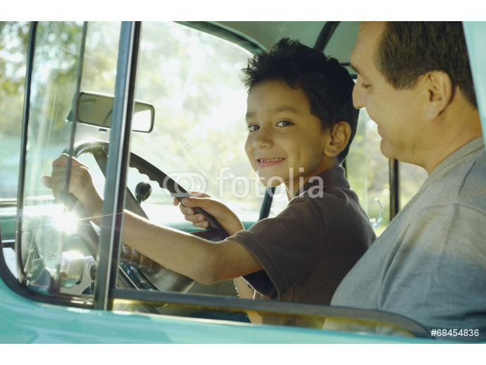 Hispanic father and son sitting in truck 64238