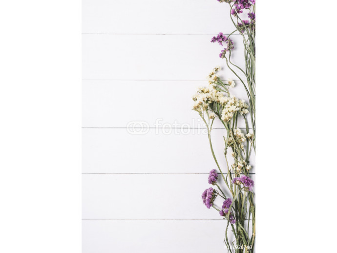 Bouquet of dried wild flowers on a white background of vintage wooden planks top view vertical 64238