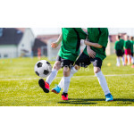 Young boy soccer players kicking ball 64238