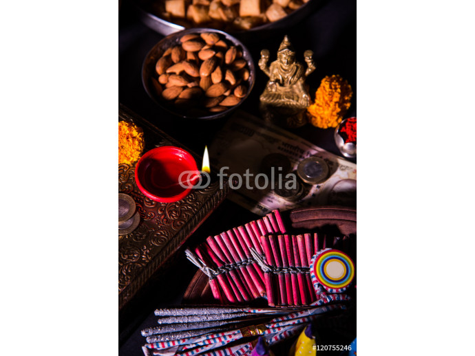 oil lamp or diya with crackers, sweet or mithai, dry fruits, indian currency notes, marigold flower and statue of Goddess Laxmi on diwali night while laxmi pujan or pooja 64238