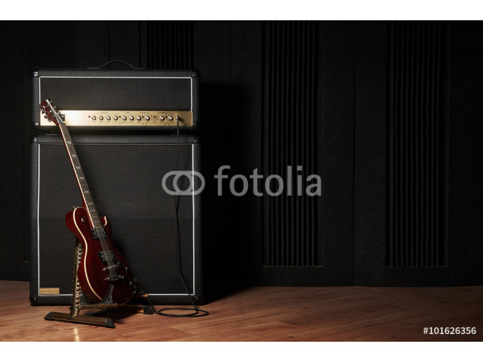Red electric guitar and classic amplifier on a dark background 64238