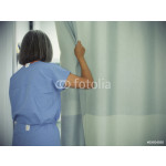Female doctor opening hospital room curtains 64238
