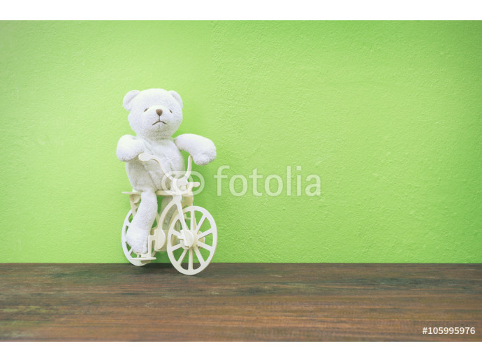 Teddy Bear toy Riding  bicycle on old wood  and green wall backg 64238