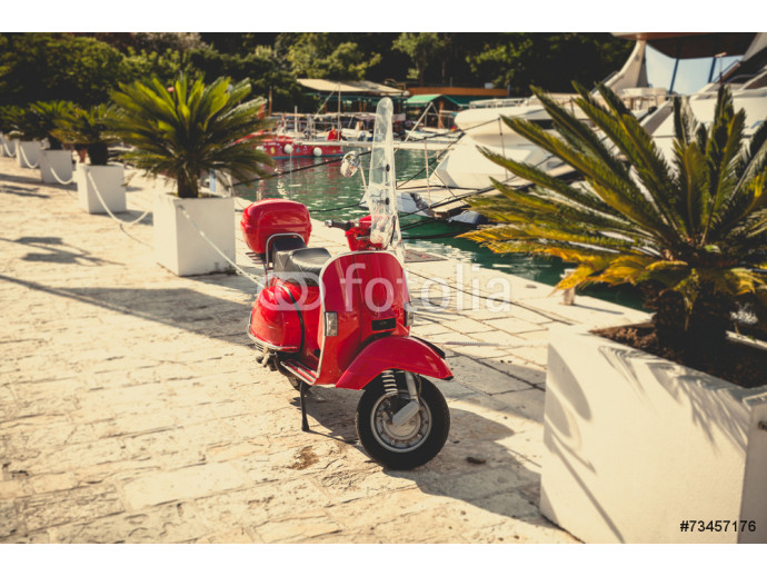 Toned photo of retro red scooter parked at port 64238