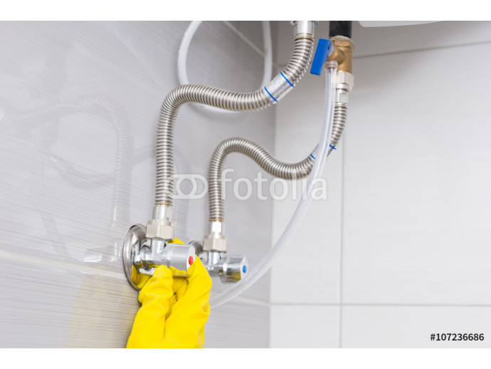 Gloved hands checking water supply valves 64238