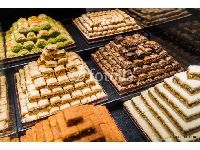Eastern sweets in a wide range, baklava, Turkish delight with almond, cashew and pistachio nuts on plates 64238