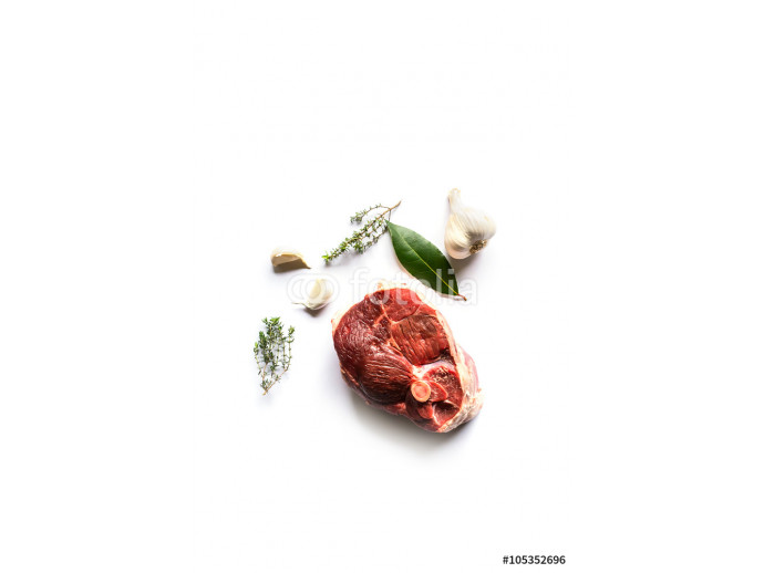 beautiful raw slice of an organic leg of lamb meat with garlic, fresh bay laurel and thyme on a white background seen from above 64238