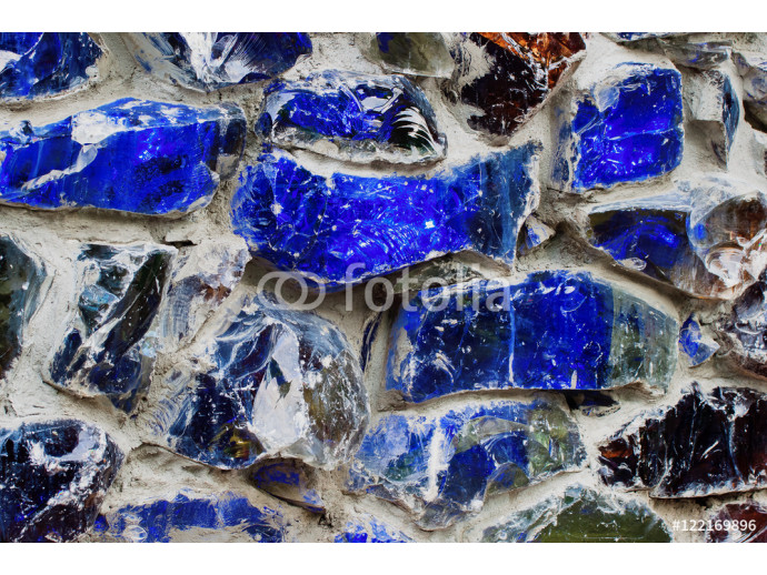 Abstract wallpaper texture of real walls, bright color. Blue , with colored stone and glass in a concrete gray wall. 64238